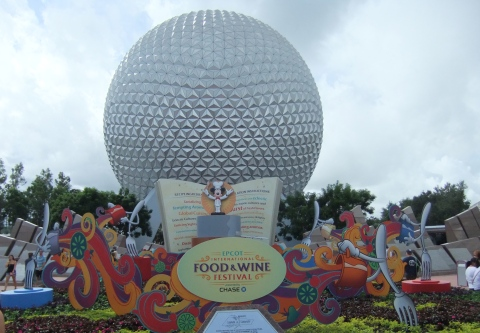 Food & Wine Festival display at the main Epcot entrance with Spaceship Earth in the background