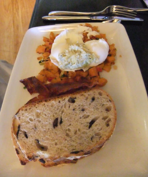 Stacked Kouzzina Breakfast: Two Poached Eggs, Kalamata Olive Toast, Artichoke Spread, and Sweet Potato Hash with Bacon